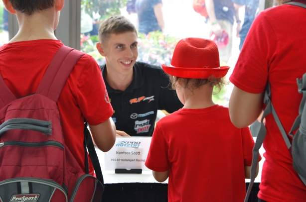 race car driver Harrison Scott signs autographs for young admirers