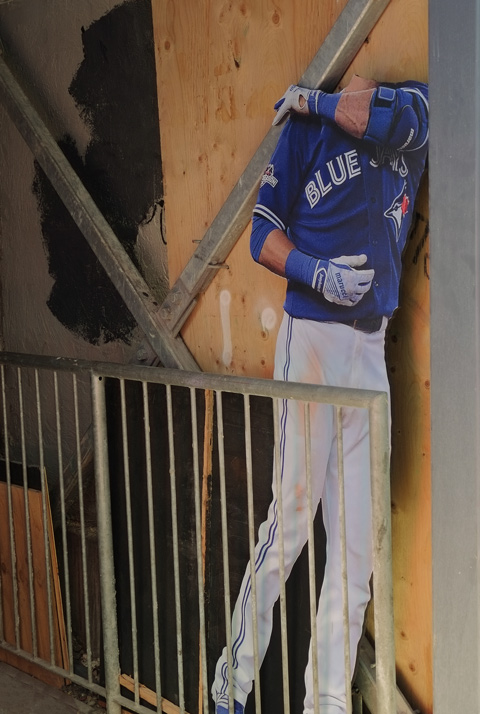 a headless cardboard cut out of a Toronto Blue Jay baseball player, in a doorway, in a lane.