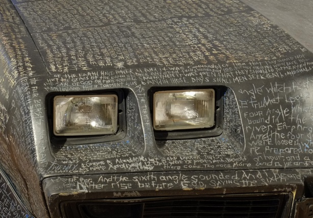 words from Revelations in the New Testament of the bible scratched into paint covering the whole surface of a trans am car, close up of the front corner of the car, headlights and part of hood