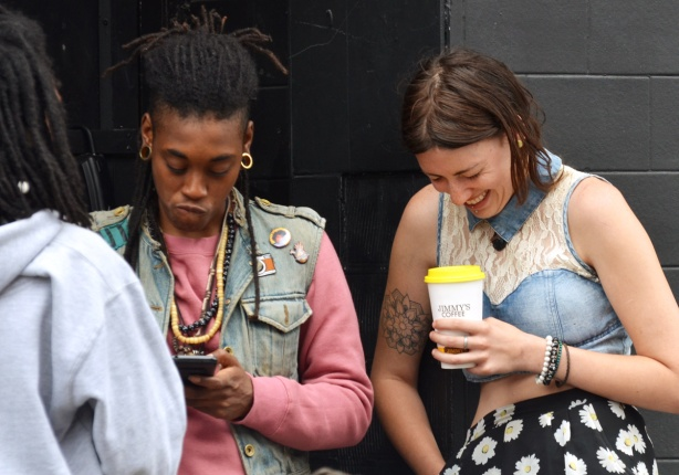 two people, one is a woman holding a coffee cup from Jimmys Coffee, she is laughing. The other is black, hair tied back, pink long sleeved shirt and sleeveless jean jacket, scowling,