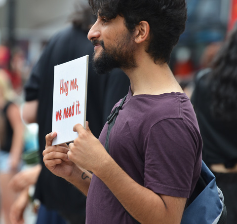 a young man holds a sign that says hug me we need it
