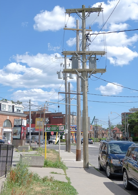 sidewalk, lined by tall hydro utility poles, wood, road, some buildings, approaching the intersection of Bathurst and Vaughan