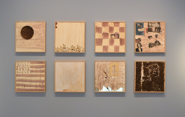 a grid of 8 square artworks by June Clark on a gallery wall