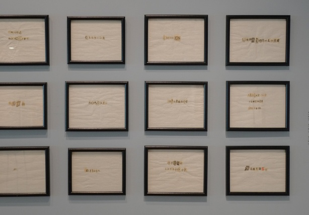 a grid of 8 square artworks by June Clark on a gallery wall - black frames around pieces of paper towel with words on them formed from cut outs from newspapers,