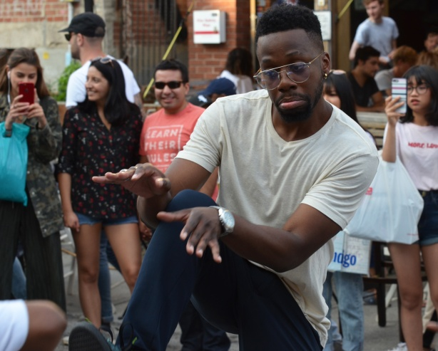 young black man dancing on the street, part of a group, Pedestrian Sunday afternoon at Kensington, people in the background watching