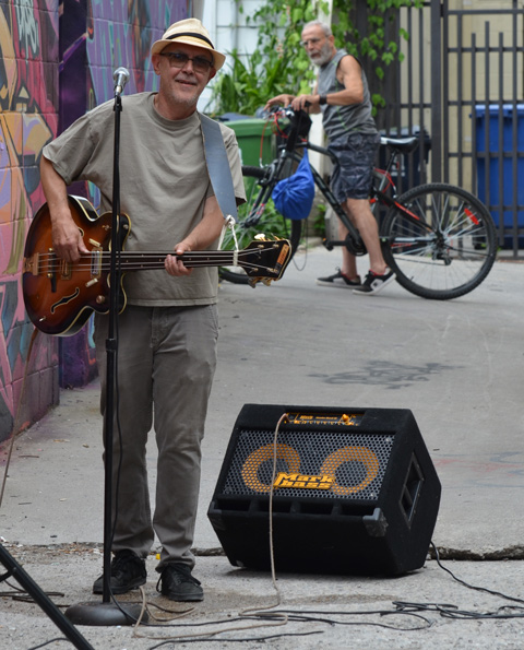 man standing in an alley with street art on one wall, holding a guitar, he has just finished playing and singing, a man is behind him on a bike