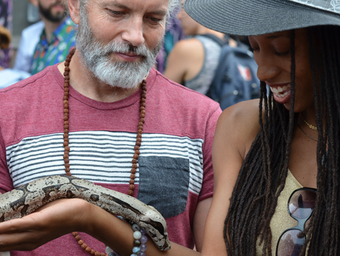 a young black woman with long dreadlocks has a large snake on her forearm, she's smiling. A man with grey grey beard and moustache watches her.