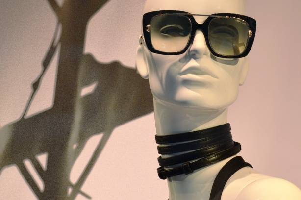 head of a mannequin in a store window, white, large sunglasses, leather rings around her neck