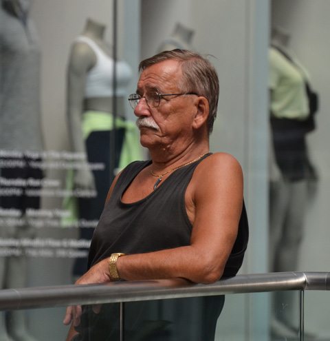 a tanned older man in sleeveless black shirt leans against metal railing at the Eaton Centre, mannequins in a store window behind him, womens' sporting wear