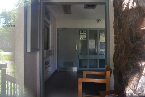 interior of medical clinic, no longer used, looking in the window, chair, posters on wall,