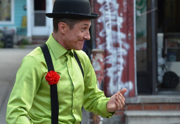 a male mime, black hamburg hat, lime green shirt, black suspenders and red carnation on the suspenders, beckoning to the crowd, outside, street festival, pedestrian sunday at kensington