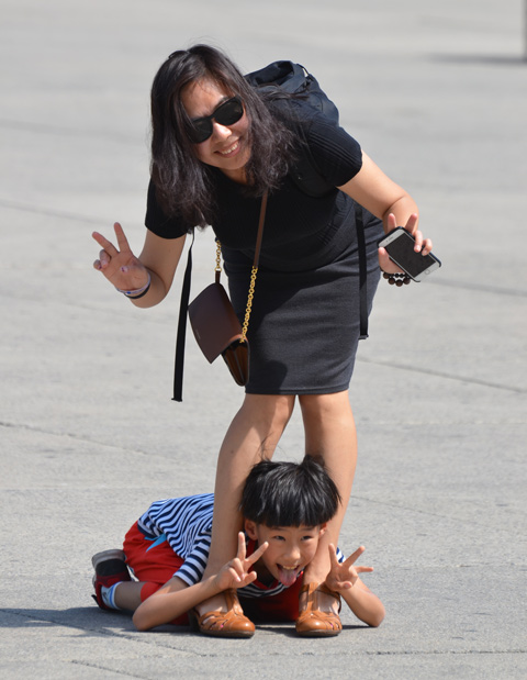 mother and son posing for picture, Asian, boy is lying on the ground between his mother's feet