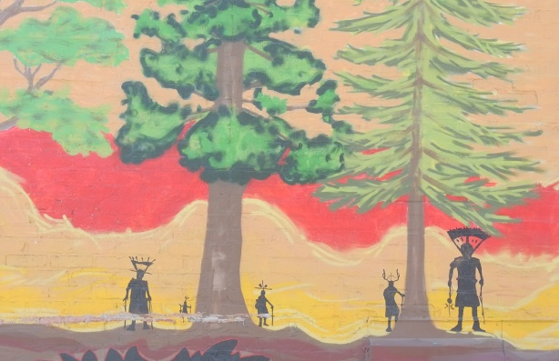 close up of mural, large trees with wavy red and yellow sky, small black figures standing under the trees