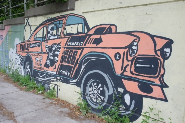 mural, by faile, orange car, woman driver, the word vanity written on the side of the car