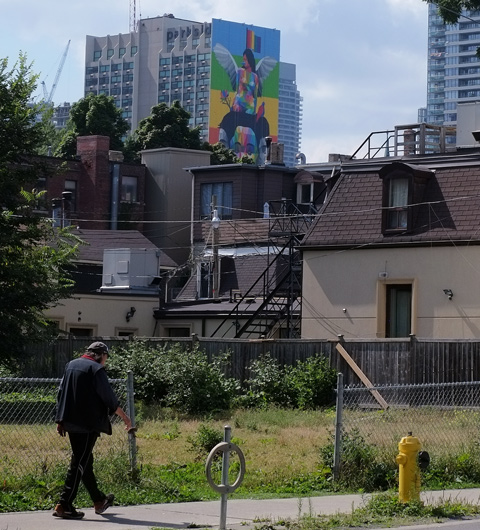 a man walks up Sherbourne street, on the sidewalk, past a vacant lot, in the background is the back of some older brick buildings and beyond that is a tall building with a mural on it, equilibrium by okudart