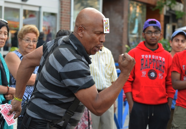 balding black man with the Queen of hearts playing card stuck on his head makes a muscle man stance with fists clenched, he's performing magic tricks while people watch him