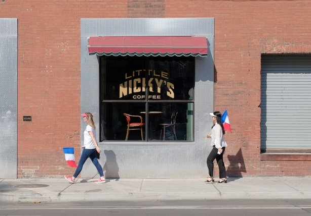 the window of Nickys coffee shop, on red brick wall, with two women walking past, both are carrying French flags
