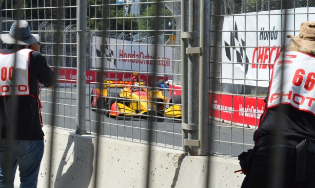 two Honda Indy official photographers get close to the race to take pictures of a yellow race car as it comes around a corner