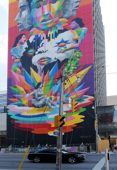 car stopped at street light at Carlton and Jarvis. Behind the car is a very tall mural, bright colours, geometric shapes, some human like figures too, with blue conical noses, equilibrium by okudart