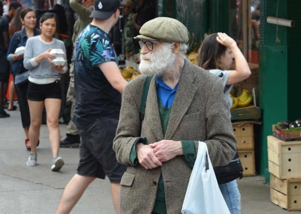 an older man in tweed jacket and cap with long white beard and mustache, black rim glasses, white plastic bag over one arm, walks down the street