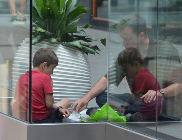 a man sits with his son on the floor of the Eaton Centre, next to the glass railing. reflections from the railing make it look like there are two boys