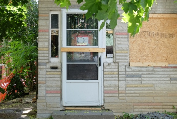 back door of an empty house, window boarded over, door with board nailed across it, open sign in the window, also a sign that says beware of dog