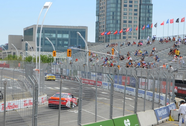 two nascar type cars racing on a track at the Honda Indy, some people sitting in the stands,