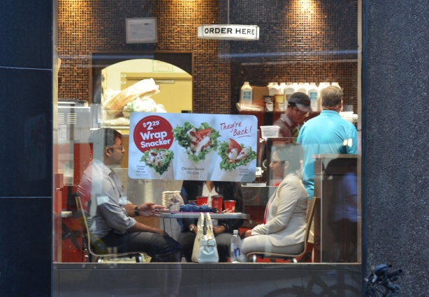 three people at Tim Hortons, sitting at a table. Seen from the outside, a poster on the window blocks the view of one of the people