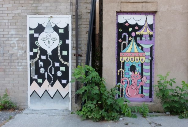 two doors in an alley, painted, one in colours, the other in black and white