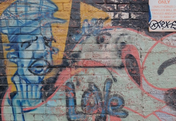 old street art, paint fading, of a blue man's face, and the word love