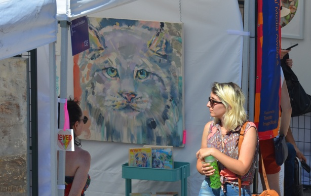 a woman walks past a painting of a cat head in blues and greys,
