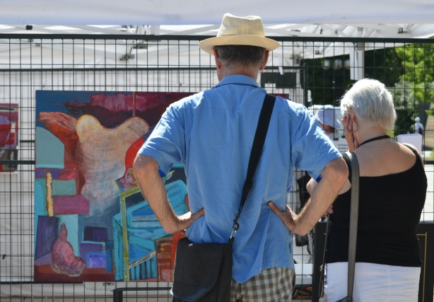 a couple looks at a painting at an outdoor art fair