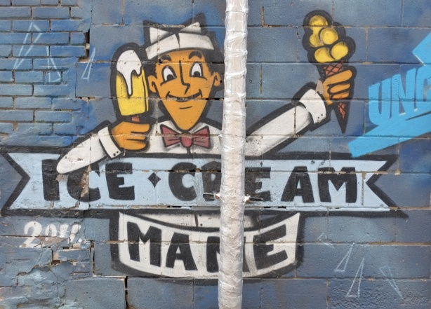 street art painting in a laneway of a man in white uniform and hat, holding popsicle in one hand and ice cream cone in the other, words say ice cream mane