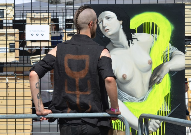 a man, with back to the camera, stands beside a painting of a topless woman, their faces are close together