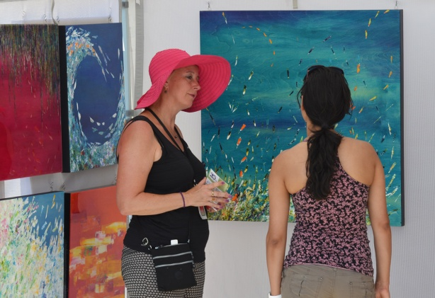 a woman in a large brimmed pink hat is talking to another woman in front of some paintings at an outdoor art fair