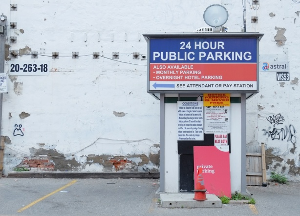 parking lot, white wall behind, parking lot attendant booth covered in signs, 24 hour public parking, private parking,