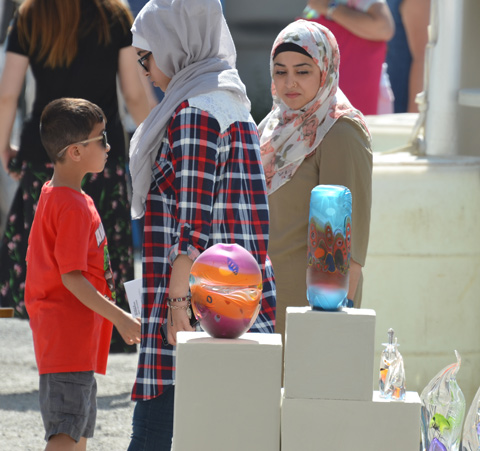 two muslim women in head scarves walk past some glass sculptures at an outdoor art fair