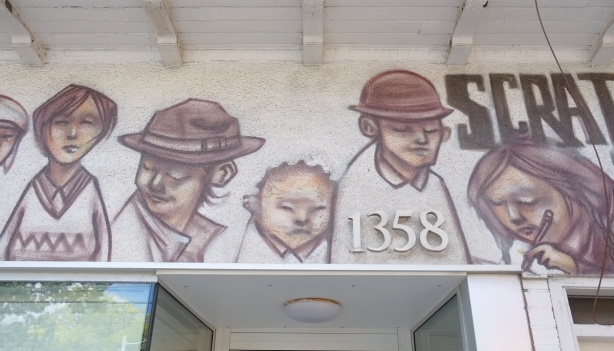 the space above a doorway at number 1358 Bathurst is painted with pictures of people (head and shoulders) in shades of brown