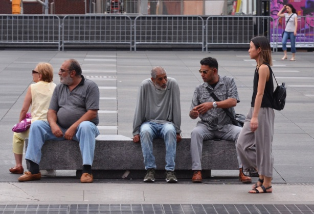 men sitting on a bench, a woman walking past