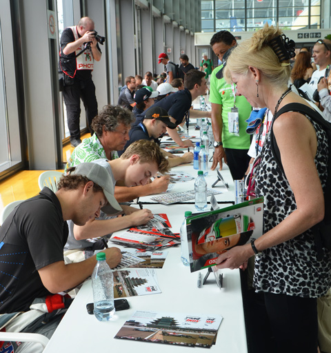 drivers of racing cars signing autographs for admirers