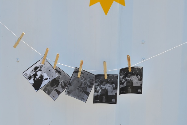 five black and white photos are attached to a string with wooden clothes pegs