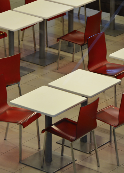 red chairs and white tables in an empty restaurant