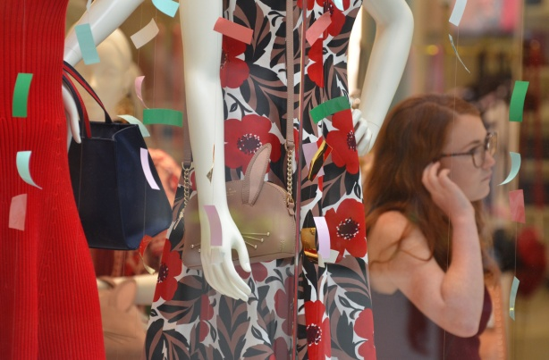 looking into the window of a women's wear store, two dresses, on mannequins, each holding a handbag. a red dress and a dress with big red flowers, a red head woman is standing beside the mannequins