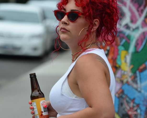 a woman in white sleeveless top and with very red dyed very curly hair, carrying a bottle of ginger beer,