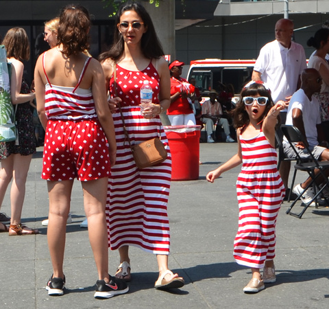 a greoup of three people in red and white clothes st Yonge Dundas square for Canada Day, a girl in a red and white striped long dress and two women in red and white polka dots and stripes