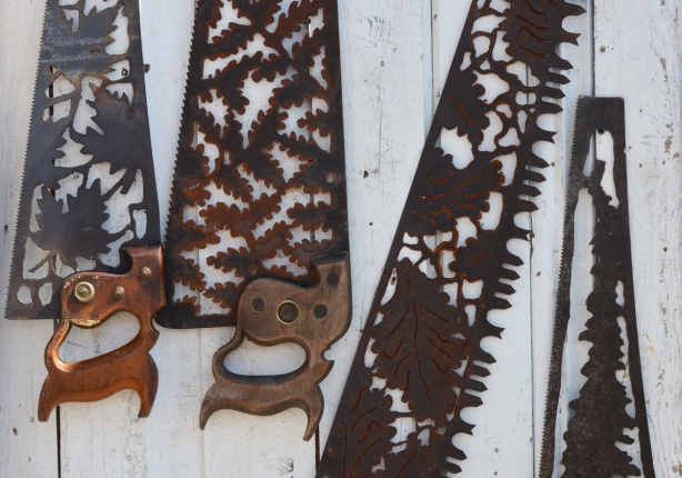 old rusty hand saws with wood handles, blades have been cut in intricate designs, one in maple leaves and the other with oak leaves