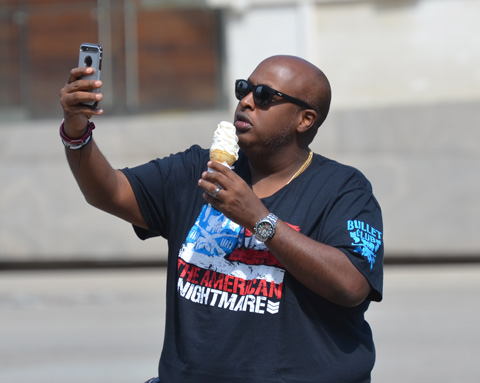 bald black man with black sunglasses is taking a selfie while holding a large ice cream cone