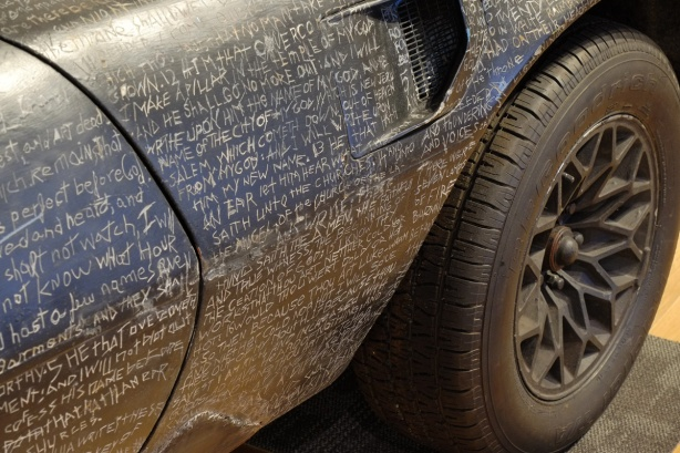 words from Revelations in the New Testament of the bible scratched into paint covering the whole surface of a trans am car, close up of the side of the car by the front passenger door, and front tire