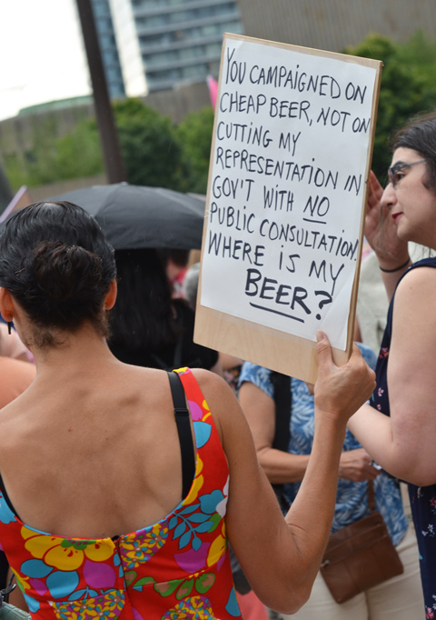 a woman holds a white hand written sign at a protest, the sign says You campaigned on cheap beer, not on cutting my representation in government with no public consultation where is my beer?