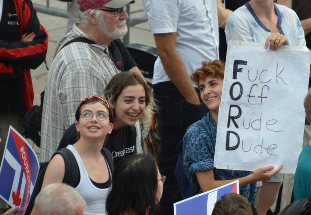 Young women in a crowd, holding a sign that says Ford - F for Fuck O for Off R for rude and D for Doug